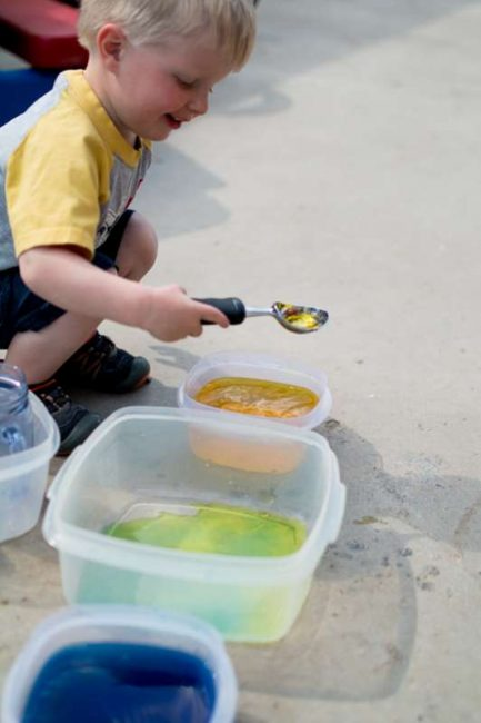 Mixing yellow and blue water together to see what it makes
