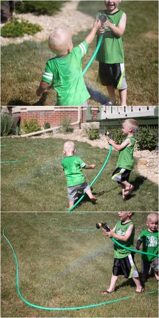 Boys making a rainbow with the water hose