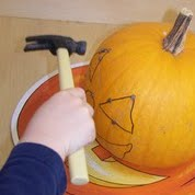 Hammering pumpkin faces. One of the 40 pumpkin activities for kids.