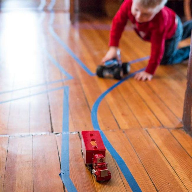 Make a tape road through rooms, make intersections, go around rugs and under tables.