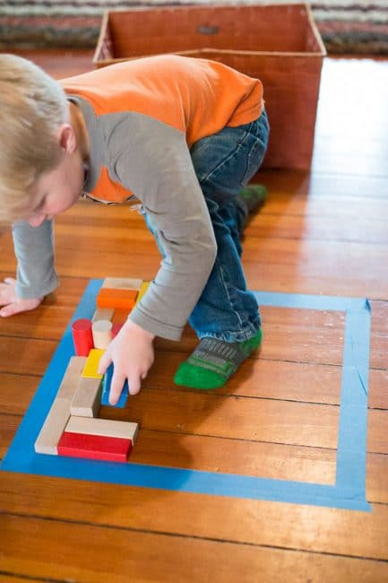Make a puzzle on the floor with a simple shape and fill it in with blocks.