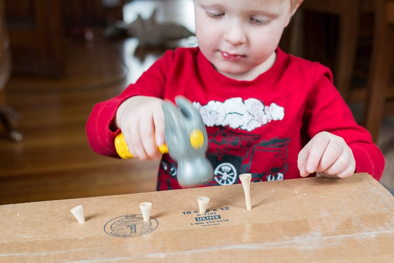 Pounding tees into a cardboard box - great idea for fine motor skills for toddlers