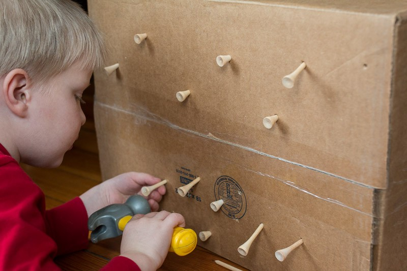 Pound tees into a cardboard box - genius idea for fine motor skills for toddlers