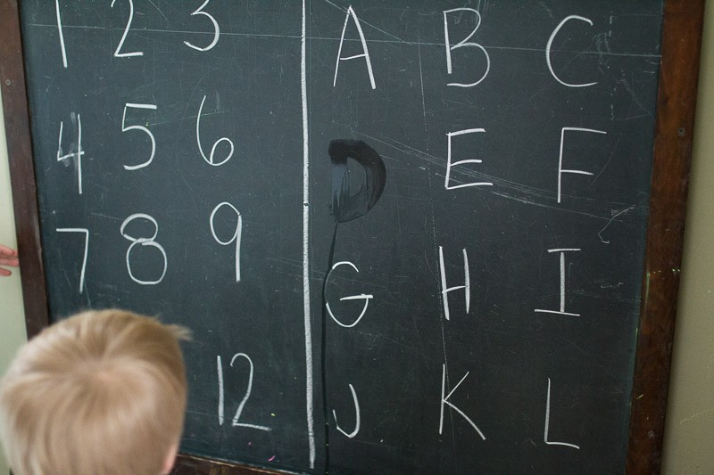 Write letters and numbers on a chalkboard to trace and erase them away