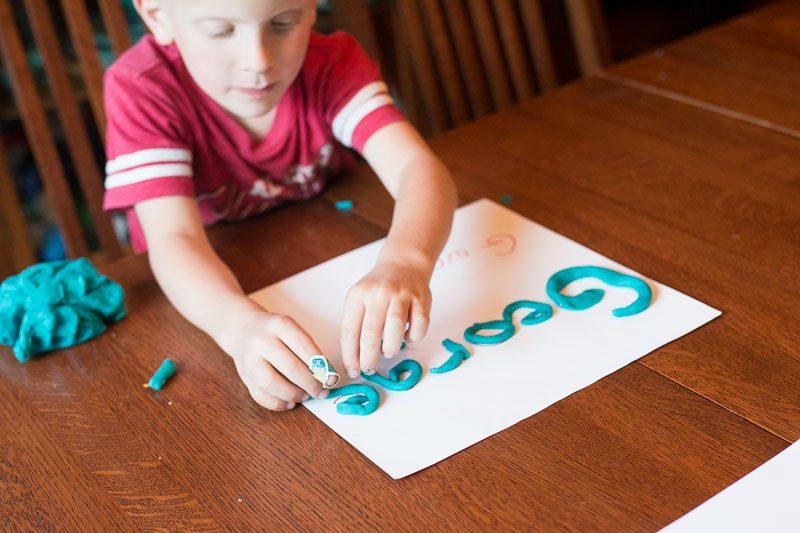 Uma atividade de massa de jogo que faz com que as crianças fortaleçam suas mãos e aprendam seu nome.