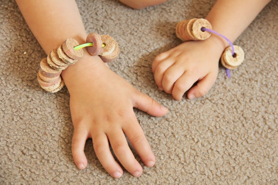 Cork bead bracelets can help kids develop and build fine motor skills like threading.