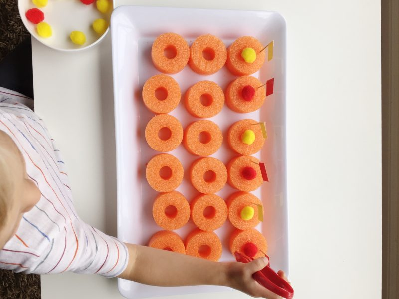 fine motor tray using pool noodles and pom poms