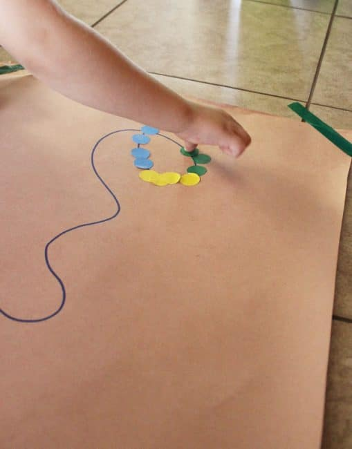 Tape down the large piece of paper, draw a wacky design with the marker, and then provide the stickers to trace the design.