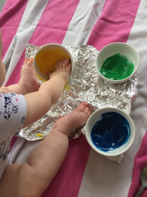 This baby foil painting art activity is messy, but so much fun! Learn how to make instant edible finger paint that's safe for you baby.