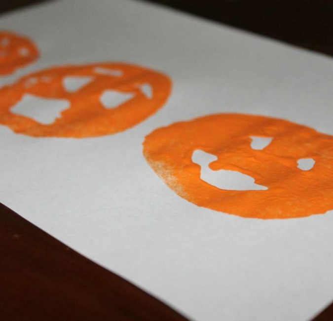 Potato stamping faces of Jack-O'-Lanterns with different emotions