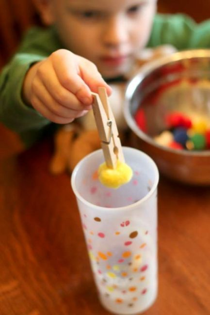 Strengthen fine motor skills using clothespins - aka the 'claw grabbing machine'