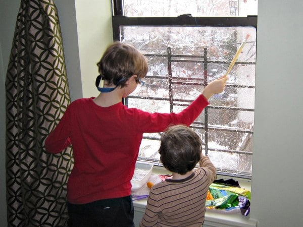 Painting the windows with soap to make the rainbow window art!