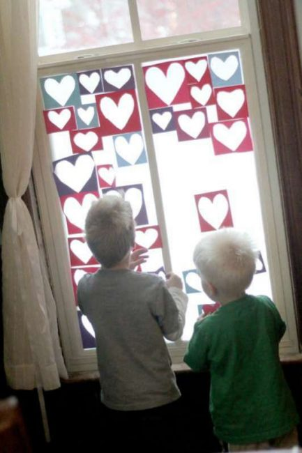 Sticking hearts to make a collage of hearts on the window